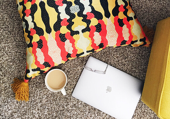 Overhead shot of a laptop, cup of coffee and Celosia Velvet floor pillow with black, red and white abstract design.