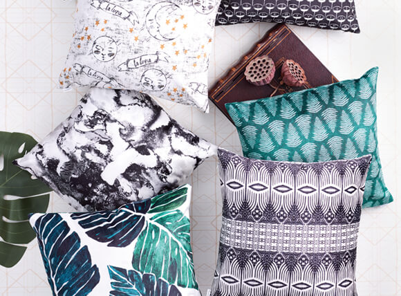 Photo of 5 square, velvet throw pillows taken from above. Designs vary from green, monstera leaves to black and white ikat designs.
