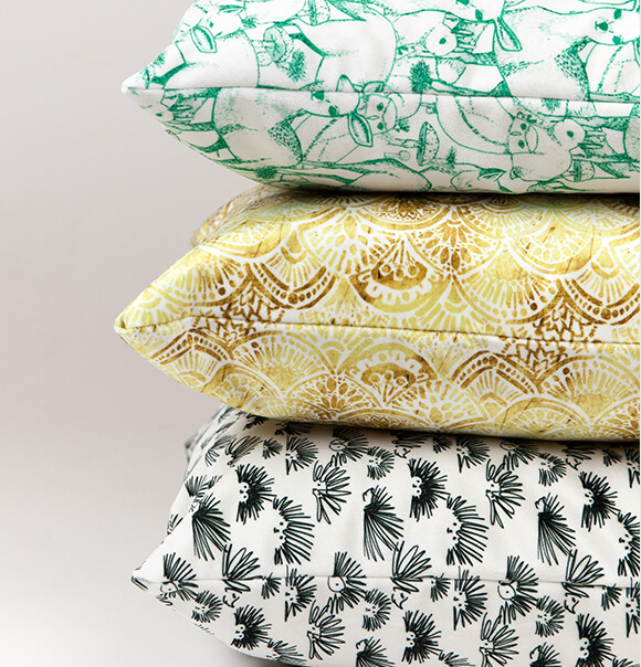 Image of 3 stacked pillows in Celosia velvet. Designs include green and white deer, gold and white art deco design and black and white hedgehog doodle.