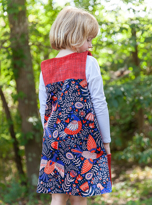 Picture of a young, blond girl from behind wearing a romper featuring a blue, white, and red Swedish folk art bird pattern.