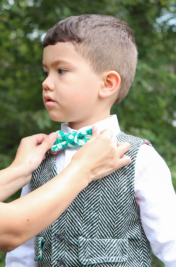 A small, dapper boy outfitted in a black and white herringbone patterned Celosia Velvet vest.