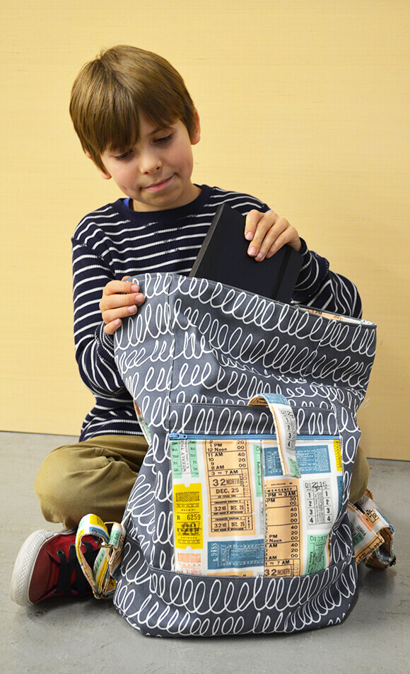 Image of a sitting boy putting a book in a black and white scribble patterened kid's backpack made from Dogwood Denim.