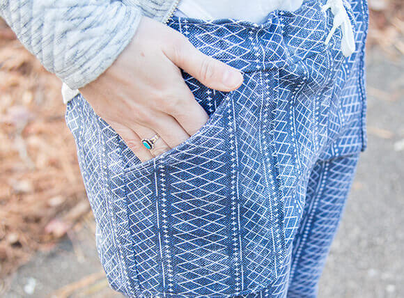 Close up image of woman wearing Dogwood Denim jeans with a small scale, white Moroccan pattern and hand in pocket.