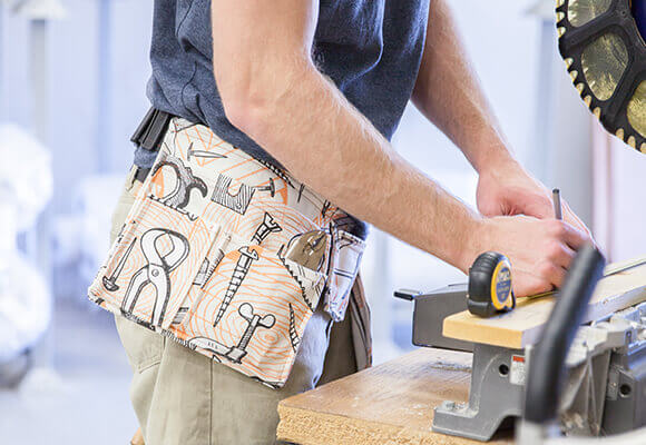 Image of a man measuring a wooden plank, wearing a tool patterned tool belt made from dogwood denim.