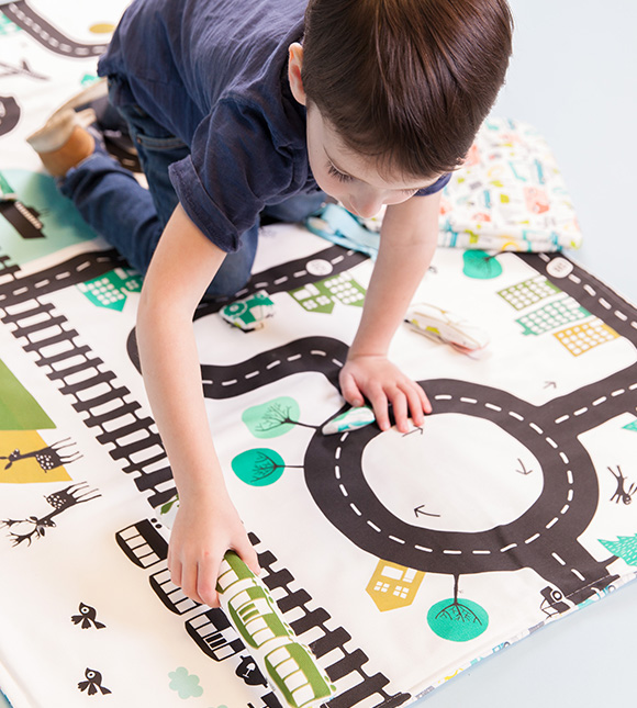 Image of a child playing with stuffed toys on a playmat made from Cypress Cotton Canvas.