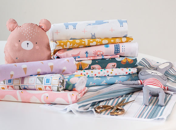 Photo of various designs printed on stacks of Petal Signature Cotton with two stuffed animal toys.