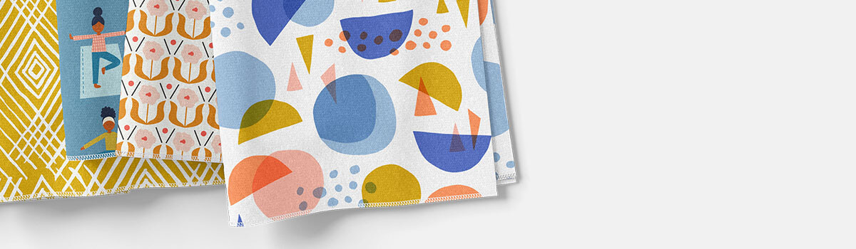 Stack of Spoonflower fabric with various designs